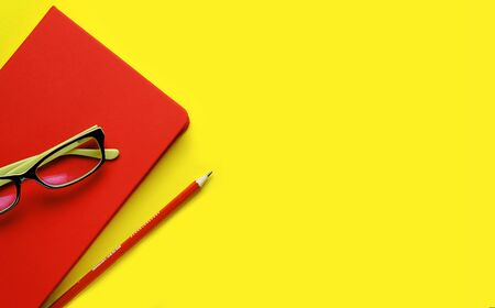 The glasses are On a Red notebook, next to a pencil, on a yellow background. Workplace Freelancer, Businessman, Entrepreneur.