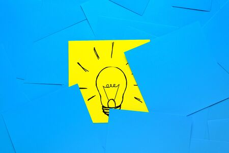 Creative drawing of a light bulb on a yellow sticker, On a background of Blue Stickers. The concept of new ideas, innovations, solutions to problems.
