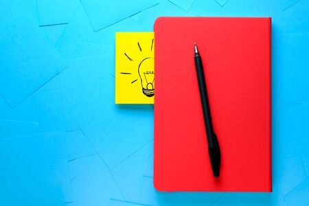 Creative drawing of a light bulb on a yellow sticker Attached To a Red Notepad. Theres A Pen Next To It. The concept of new ideas, innovations, solutions to problems. Stok Fotoğraf