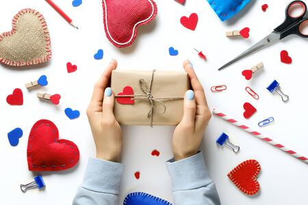 Womens hands hold a gift in wrapping paper, for Valentines Day. Red And Blue Decorative Valentines And Hearts, Stationery, Scissors. The concept of handmade.