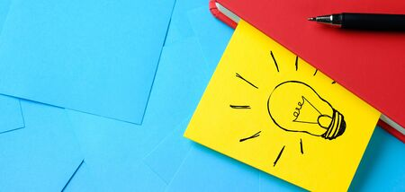 Creative drawing of a light bulb on a yellow sticker Attached To a Red Notepad. Theres A Pen Next To It. The concept of new ideas, innovations, solutions to problems. Banner