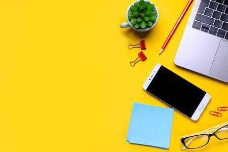 Glasses, mobile phone, laptop, flower, stickers, paper clips, stationery on a yellow background. Workplace Freelancer, Businessman, Entrepreneur.