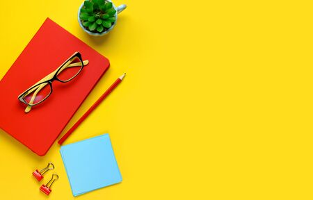 The glasses are on a pink notebook, next to a pencil, on a yellow background. There Was A Pencil, Stickers, Paper Clips, And A Flower. Workplace Freelancer, Businessman, Entrepreneur.