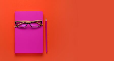 The glasses are lying on a pink notebook, next to a pencil, against a background of lush lava. Workplace Freelancer, Businessman, Entrepreneur. Banner Stok Fotoğraf