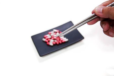 sobredosis: Es necesario, sobredosis de drogas, en la placa de cerámica cuadrado negro El consumo de drogas que, Comer con palillos