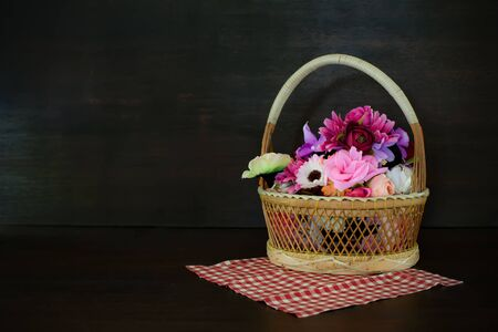 colorful artificial flowers made from cloth in basket on wooden table. with clipping part. Stock Photo