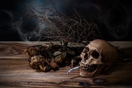 the kills: Still life Smoking human skull with cigarette on wooden table, people smoke cigarette look like trying to commit suicide, In the day  World No Tobacco Day please quit or stop smoke for good health.