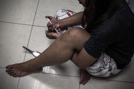 sobredosis: sobredosis asiático mano femenina adicto a las drogas, jeringuilla drogas estupefacientes en acción