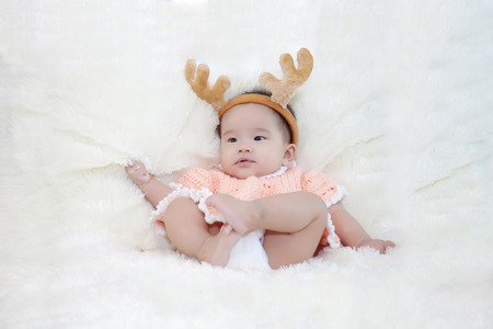 innocent girl: Cute five months asian baby in reindeer horns., on bright soft carpet. Stock Photo