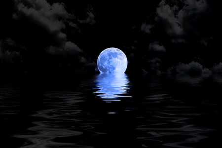 water reflection: dark blue full moon in cloud with water reflection closeup showing the details of the lunar Stock Photo