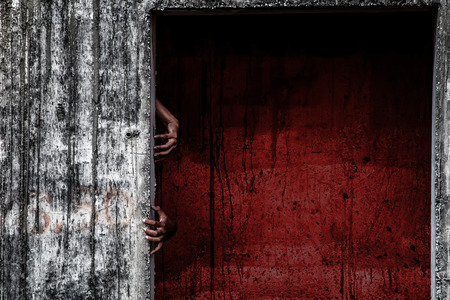 scary abandoned building with blood wall and ghost hand coming out of a door