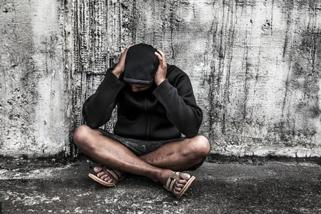 dependent: overdose asian male drug addict with problems, man in hood with hands on his head