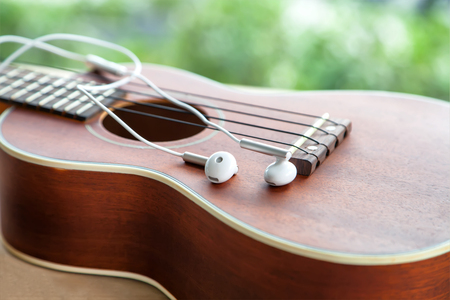earphone: close-up of earphone with ukulele guitar on wooden table in the garden Stock Photo