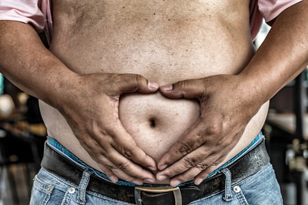 fatness: The Dangers of Belly Fat. Obese Man in Jeans Squeeze the Belly Fat. Stock Photo