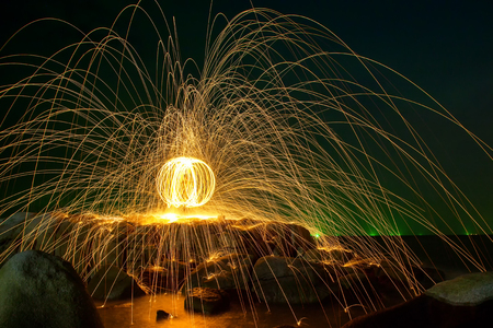 steel wool: Hot Golden Sparks Flying from Man Spinning Burning Steel Wool into a Sphere on a Rocky Shoreline., Long Exposure Photography using Steel Wool Burning. Stock Photo