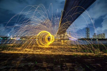 steel wool: Hot Golden Sparks Flying from Man Spinning Burning Steel Wool under Bhumibol Bridge in Bangkok Thailand., Long Exposure Photography using Steel Wool Burning.