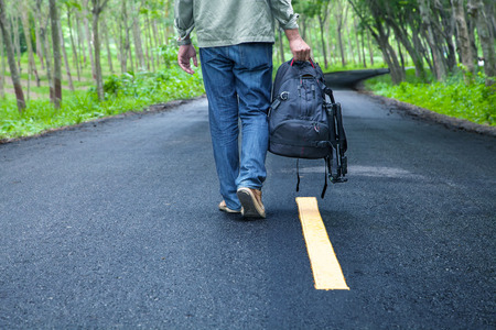 Hitchhiking tourism concept. Travel hitchhiker man with backpack walking on the road passes through beautiful forests.