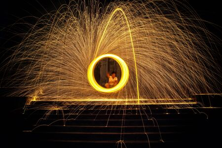 steel wool: Hot Golden Sparks Flying from Man Spinning Burning Steel Wool on the Stair., Long Exposure Photography using Steel Wool Burning.