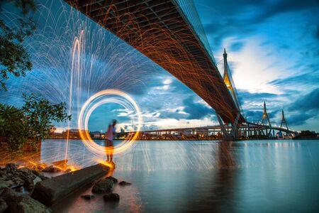 Caliente chispas de oro que vuelan desde hombre gira Burning lana de acero bajo el puente de Bhumibol en Bangkok, Tailandia., Fotografía Exposición larga usando Burning lana de acero.