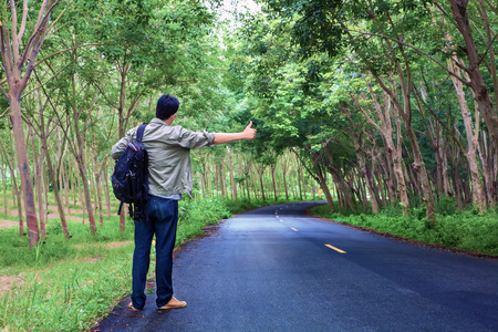 Hitchhiking tourism concept. Travel hitchhiker man carrying backpack walking on the road passes through beautiful forests.
