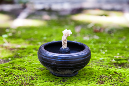 close-up of empty traditional clay lamp on the green moss ground. (shallow depth of field and selective focus)