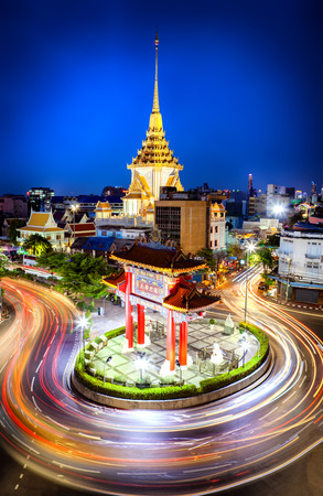 The gateway arch (Odeon Circle) and Traimit temple behind with light trails from long exposure photo taken, Landmark of Chinatown Bangkok Thailand. (Chinese character is meant Long Live the King) Stock Photo