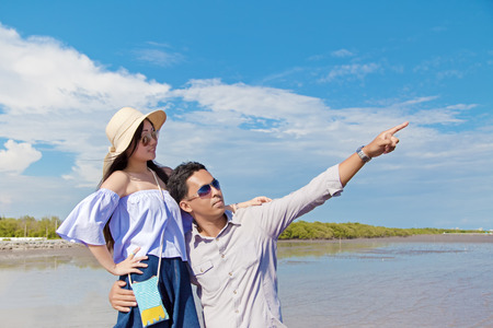 Romantic Asian couple embracing together with love and happiness feeling under blue sky and sunlight in the afternoon on the seashore. Banco de Imagens