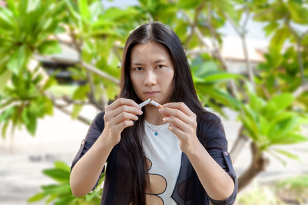 Young beautiful woman holding broken cigarette, people smoke cigarette look like trying to commit suicide, In the day  World No Tobacco Day please quit or stop smoke for good health.
