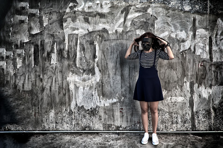Beautiful woman in black mask standing in scary abandoned building. Concept of wickedness, sadness, depressed and human problems in dark tone.