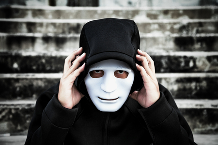 Asian man in the black hood and white mask with confused depression sitting on stairs, in scary abandoned building, The concept of unemployed, sadness, depressed and human problems in dark tone.