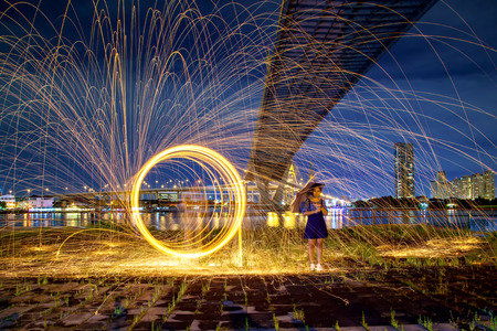 Beautiful woman with umbrella and hot golden sparks rain from man spinning burning steel wool under Bhumibol Bridge in Bangkok Thailand., Long Exposure Photography using Steel Wool Burning. Stockfoto