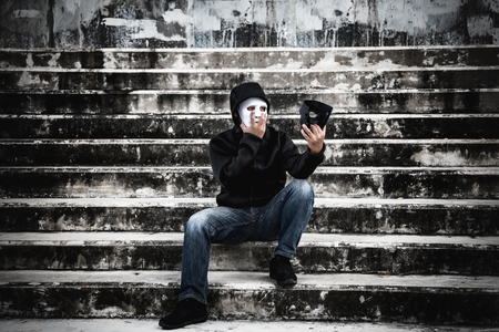 Asian man in the black hood and white mask with confused depression sitting on stairs and looking at black mask, in scary abandoned building, Human face expression, Good and Bad temptation concept. Banco de Imagens
