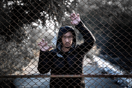 Depressed man wearing a black hoodie standing behind a fence hand grabs steel mesh cage, no freedom Banco de Imagens