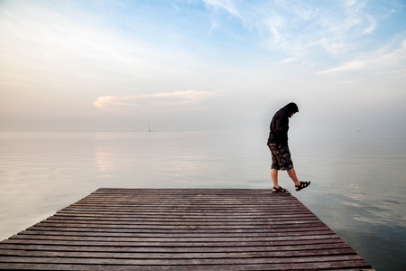 Suicide concept., Depressed young man wearing a black hoodie standing on wooden bridge extended into the sea looking down at his shoe and contemplating suicide., On the edge of a bridge with sea below. Banco de Imagens
