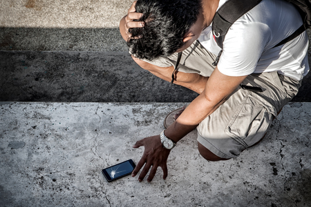 man hold the head with hand and grab a broken smartphone with crashed screen on the concrete floor.