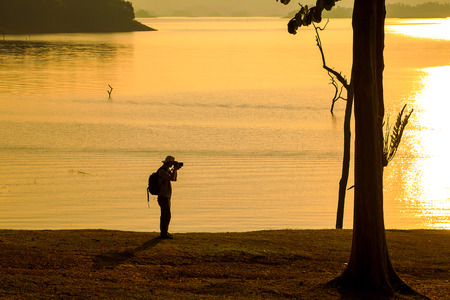 Silhouette of photographer taking a photo near the lake., with beautiful light of sunset behind.