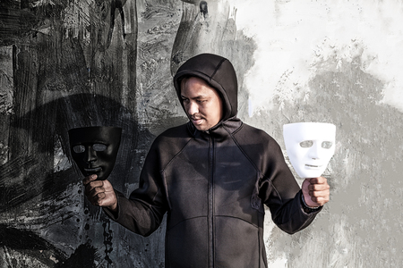 Asian man chooses between black and white mask in scary abandoned building, Human face expression, Good and Bad temptation concept. Banco de Imagens