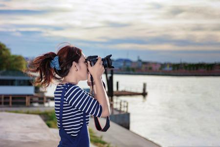 Beautiful photographer taking a photo near Chao Phraya River in Bangkok, Thailand.