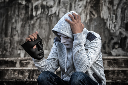Asian man in the hood and white mask with confused depression sitting on stairs and looking at black mask, in scary abandoned building, Human face expression, Good and Bad temptation concept.