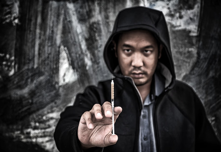 junkie: Drug abuse concept., overdose asian male drug addict hand with drugs narcotic syringe in action. Stock Photo