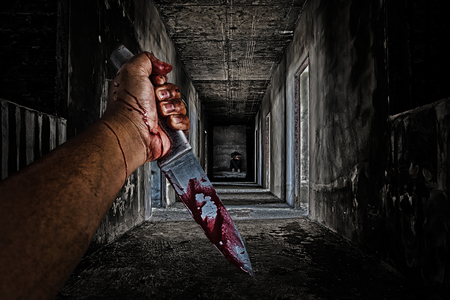 hand holding knife smeared with blood and some people sitting in the room at end of scary hallway walkway in abandoned building. Stockfoto