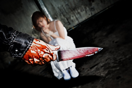 Murderer bloody hand holding knife smeared with blood ready to attack and kill his victim., that is scared woman bound hands with rope., missing kidnapped., in abandoned building., in dark tone. Foto de archivo