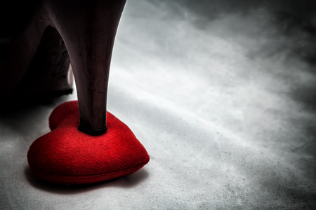 women shoes stomp on broken heart in dark tone., unrequited love., love concept for valentines day.