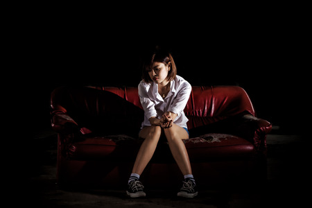 Unhappy lonely depressed woman sitting on old couch and contemplating suicide, in scary abandoned building, Concept of unemployed, sadness, depression, broken heart and human problem in dark tone.