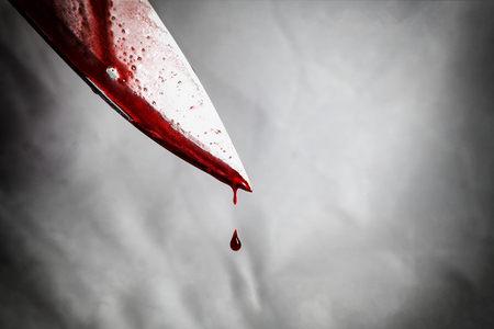 close-up of man holding knife smeared with blood and still dripping. Foto de archivo