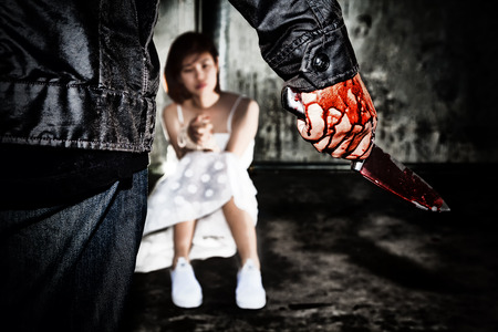 Murderer bloody hand holding knife smeared with blood ready to attack and kill his victim., that is scared woman bound hands with rope., missing kidnapped., in abandoned building., in dark tone. Stockfoto