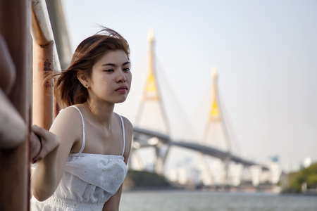 Broken heart woman crying and tears coming from her eyes., suffering from relationship and love problem., after a fight with boyfriend., at pier near the river with blurred city background.