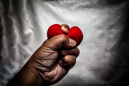 angry man crushing red heart in hand., unrequited love., love concept for valentines day., in dark tone.