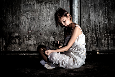 Drug abuse concept., overdose asian female drug addict use syringe injection narcotic to her hand., in scary abandoned building., In dark tone. Standard-Bild