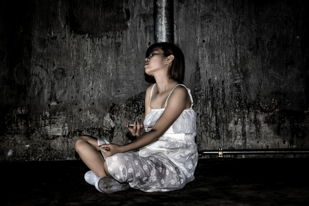 Drug abuse concept., overdose asian female drug addict use syringe injection narcotic to her hand., in scary abandoned building., In dark tone. Stockfoto
